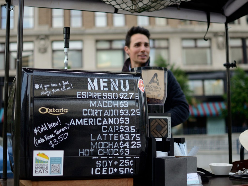 man sells espresso and coffee at stand in boston