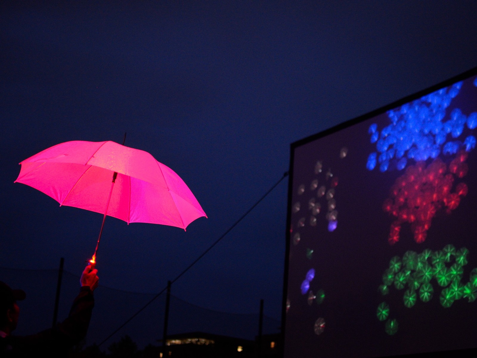man holding pink led light umbrella project at mit