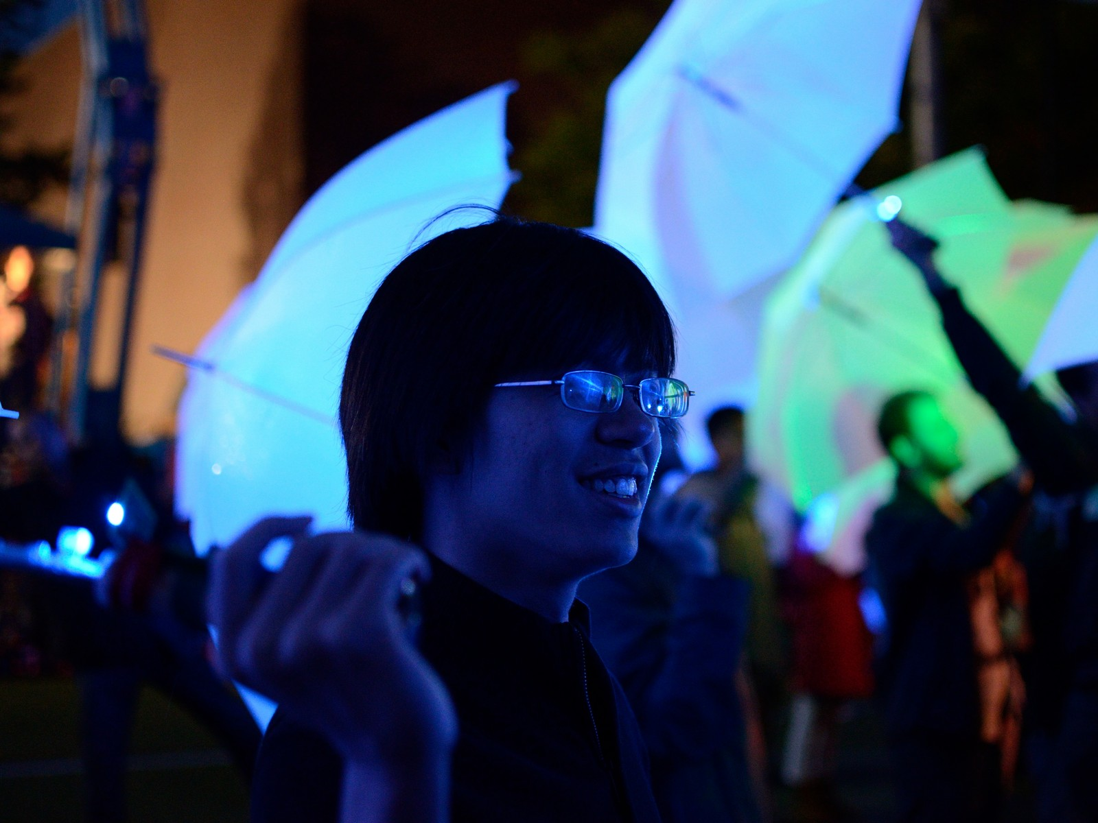 norman cao holds an umbrella in the crowd at umbrella project mit