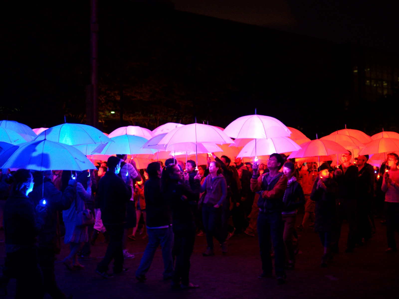 crowd holds led light umbrella at umbrella project mit